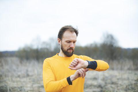 un corredor controla en su smartwatch las pulsaciones y el ritmo cardiaco de su carrera