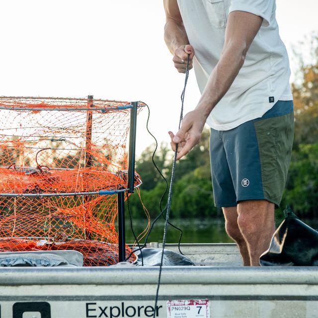 man wearing roark boatman boardshorts standing in boat fishing