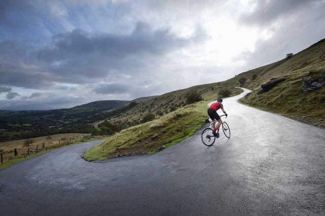 road cyclist climbing hairpin bends up hillside