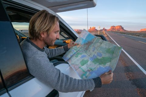 road trip concept young man outside car looking at road map for directions exploring national parks and nature ready for adventure