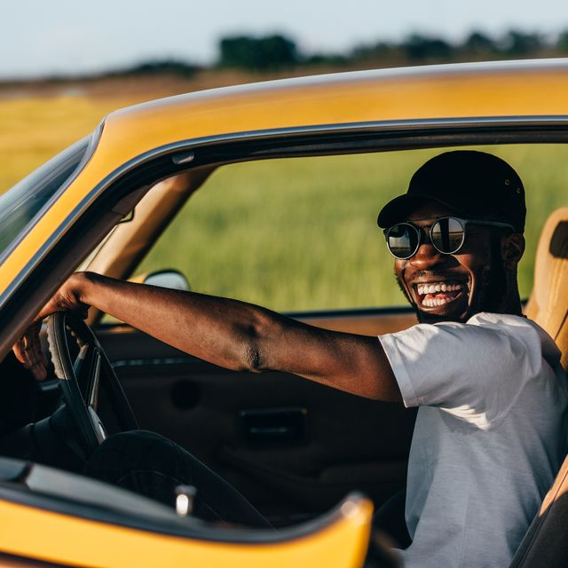 man in sunglasses and hat driving car