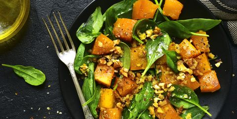 Roasted pumpkin salad with spinach and walnut .Top view.