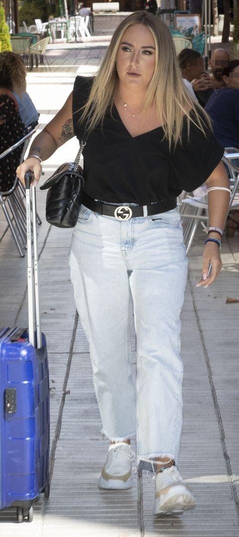 la hija de antonio david flores, con una camiseta negra y un vaquero, empuja una maleta
