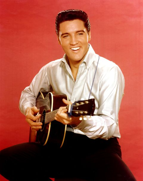 Rock and roll musician Elvis Presley strums an acoustic guitar