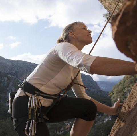rock climber looks upwards to route above, sunrise