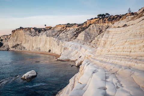 rock formations by sea at scala dei turchi
