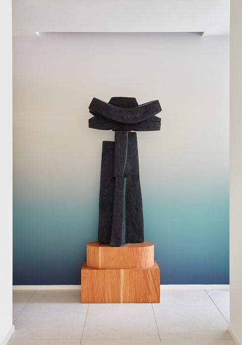 escultura negra abstracta sobre peana de madera, la pared del fondo con degradado en tonos azules en la casa houston mid century de jamie bush