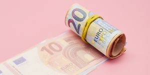 Roll of Euro banknotes on pink background