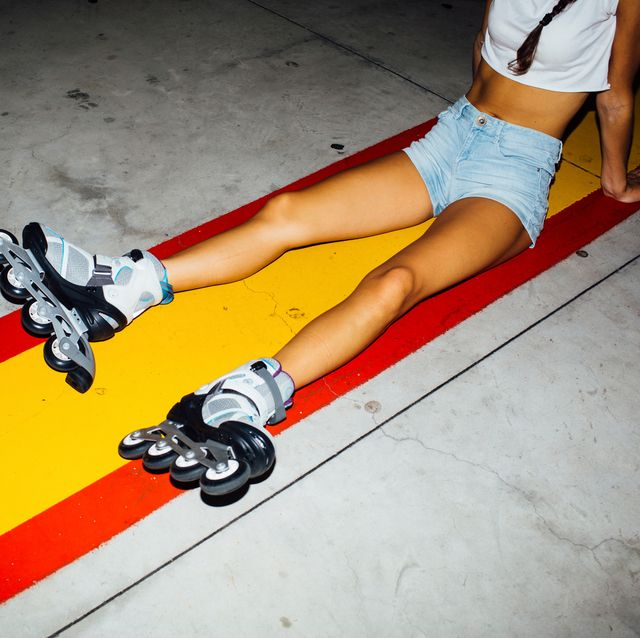 young woman with roller skates sitting on concrete
