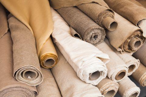Rolls of  linen cloth lie on counter