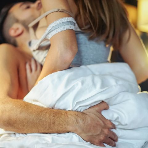 Romantic Couple Lying Down On Bed At Home