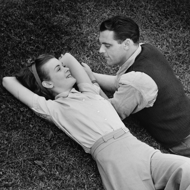 Romantic couple lying on grass, (B&W), elevated view