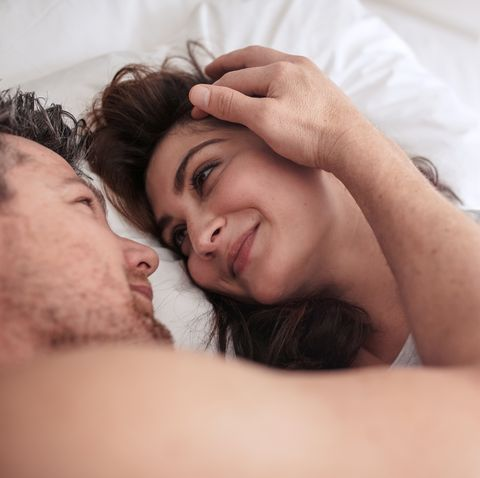Romantic couple lying together on bed