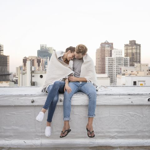 Romantic couple sitting on rooftop terrace, enjoying the view