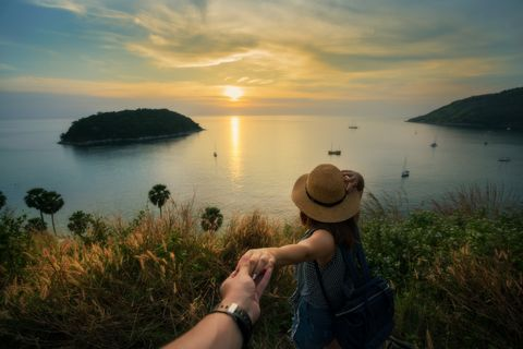 Romantic scene of young love couple holding hand in view point look sunset at Promthep Cape Phuket, Thailand.