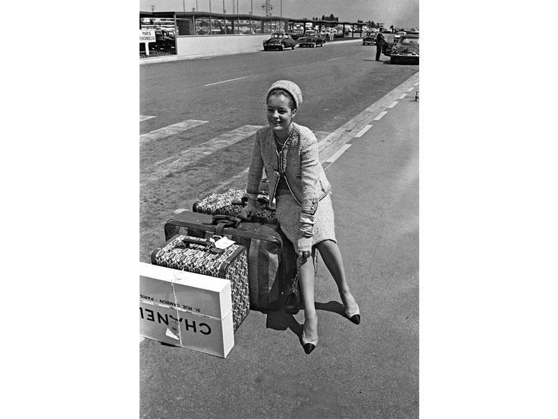 Romy Schneider indossa un completo in tweed, scarpe bicolore e la borsa Chanel 2.55 a Parigi nel 1962.
