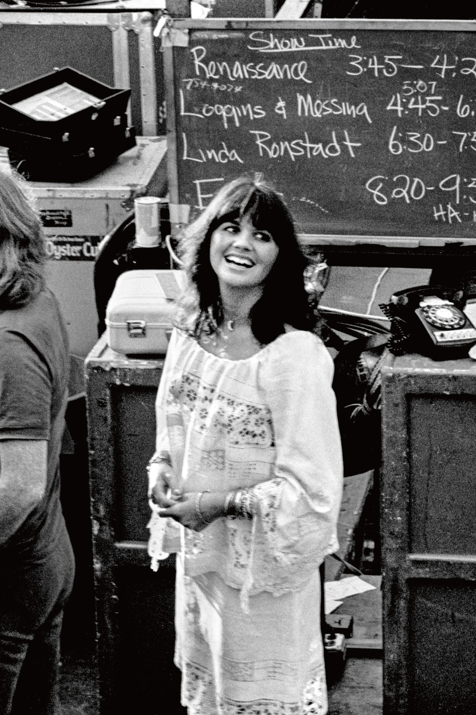 "Linda Ronstadt backstage at Day on the Green in 1976. ""The chalkboard behind her lists the order in which the bands would perform,"" Resnick writes in his book."
