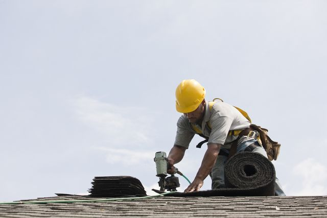 roofer working on shingling a new roof