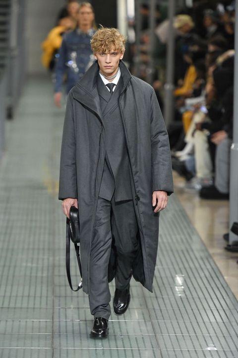 modelo en el desfile de alyx con traje de chaqueta y abrigo oversize