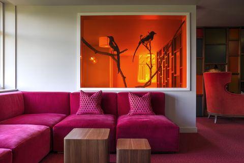 Room, Couch, Living room, Furniture, Interior design, Orange, Lighting, Magenta, Wall, Modern art,