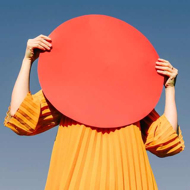 woman holding red circle over her face