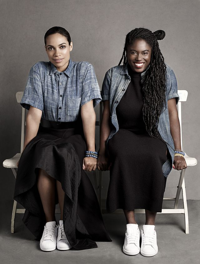 rosario dawson and abrima erwiah sit on a white bench smiling