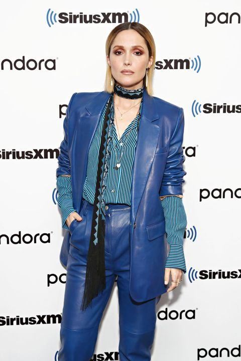 actress rose byrne poses for a photo, wearing a striped button up shirt and a blue blazer