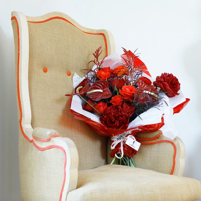 rose color meanings   red rose bouquet on chair
