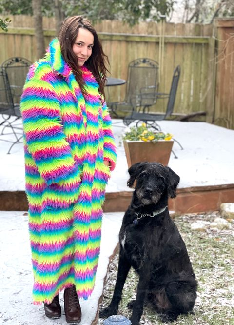 the author of the story rose minutaglio wearing her oversized technicolor coat with stripes of pink, green, yellow, and blue outside in austin, texas, when start started falling her 100 pound black hound dog stands next to her looking very cute