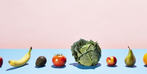 A row of different fruits and vegetables on a table top