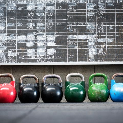 row of kettlebells against wall at gym