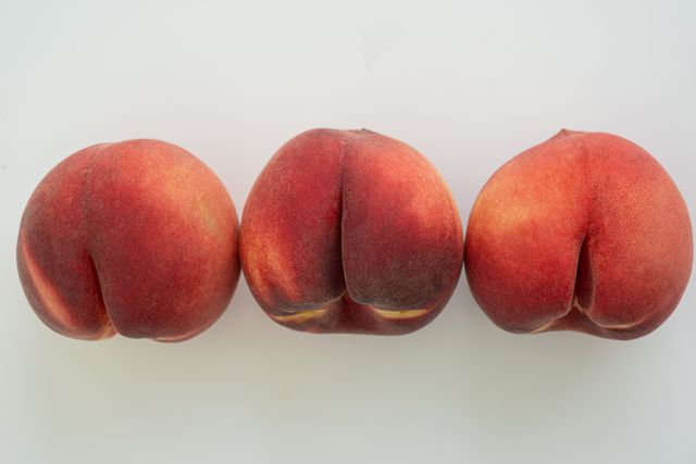 a row of white peaches on white surface beso negro