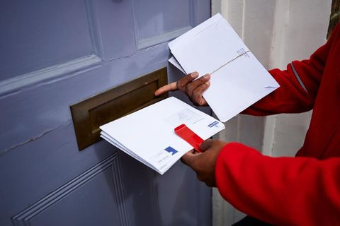 Royal Mail delivery worker delivering letters/mail