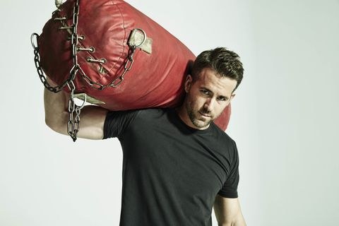 ryan reynolds, ryan reynolds workoutactor, wearing a black t shirt, holding a large, red punching bag on one shoulder