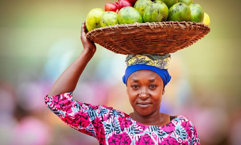 Rwandan woman carrying basket full of fruits
