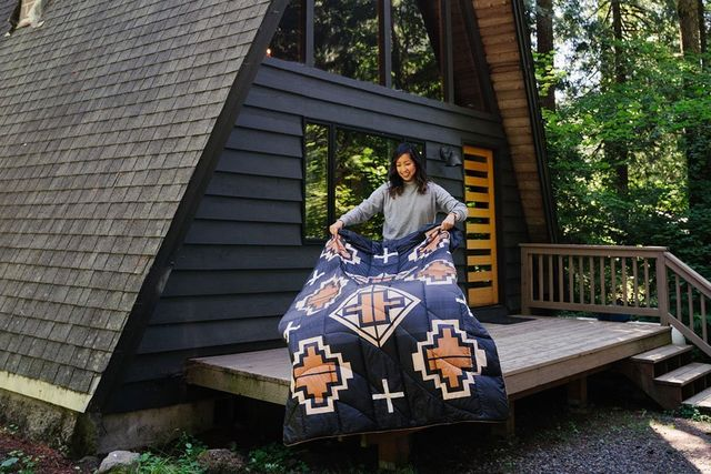 a woman shaking out an insulated blanket on a deck