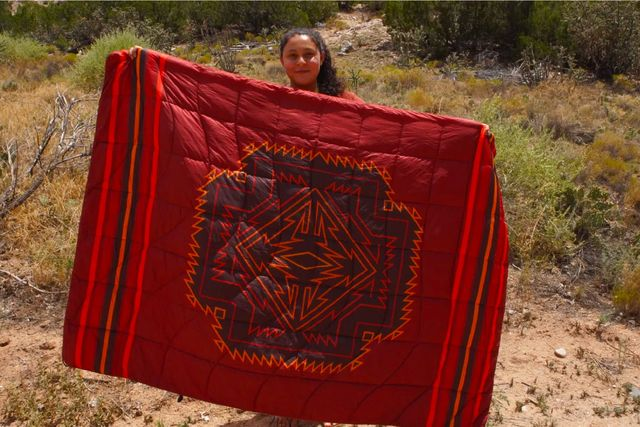 a woman holding up a red patterned blanket