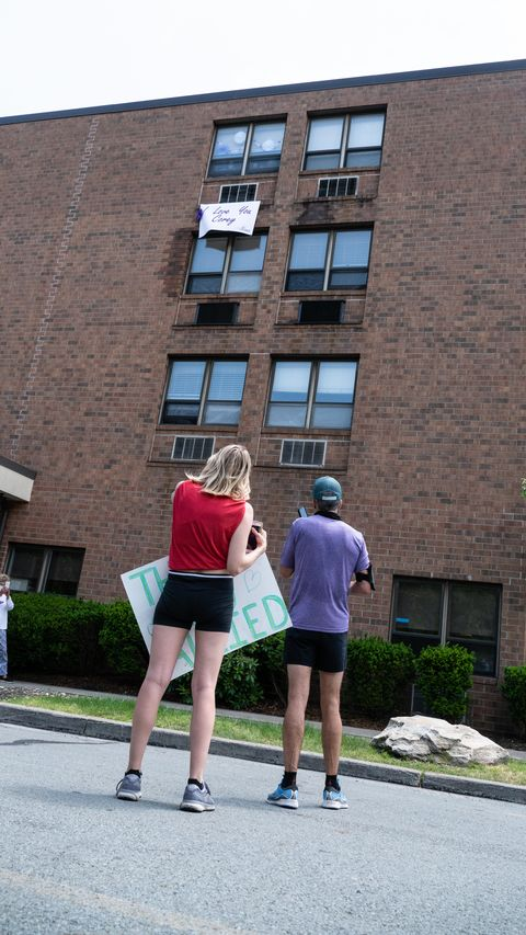 "corey cappelloni speaks to his grandmother, ruth, via microphone and speakers ruth lived on the fourth floor and hung a sign out of her window that read, ""i love you, corey   nana"""