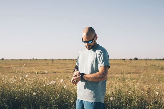 runner adjusting his smartwatch before his morning workout in the countryside
