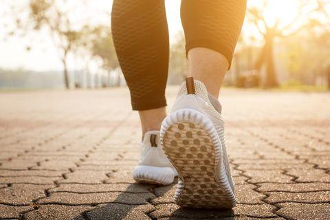 Pés de corredor correndo na estrada closeup no sapato.
