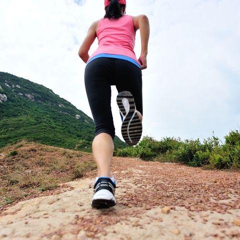 runner legs running on seaside mountain trail