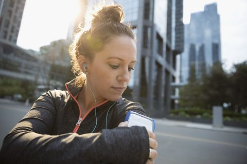 Female runner adjusting mp3 player arm band, listening to music with earbud headphones on urban street