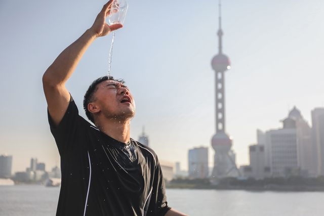 runner pouring water over his head with famous skyline of lujiazui financial district, the bund, shanghai