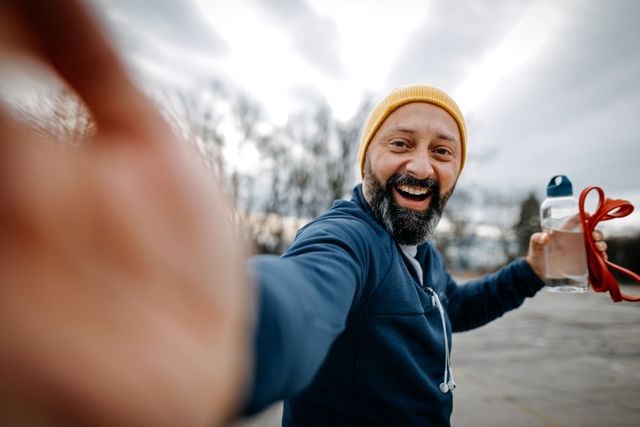 happy mature man with knit hat taking a selfie and holding water bottle and resistance band during jogging outdoors