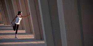 Runner stretching on concrete pillar