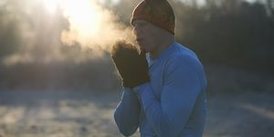 Runner wearing knit hat and gloves, rubbing hands together, breathing cold air