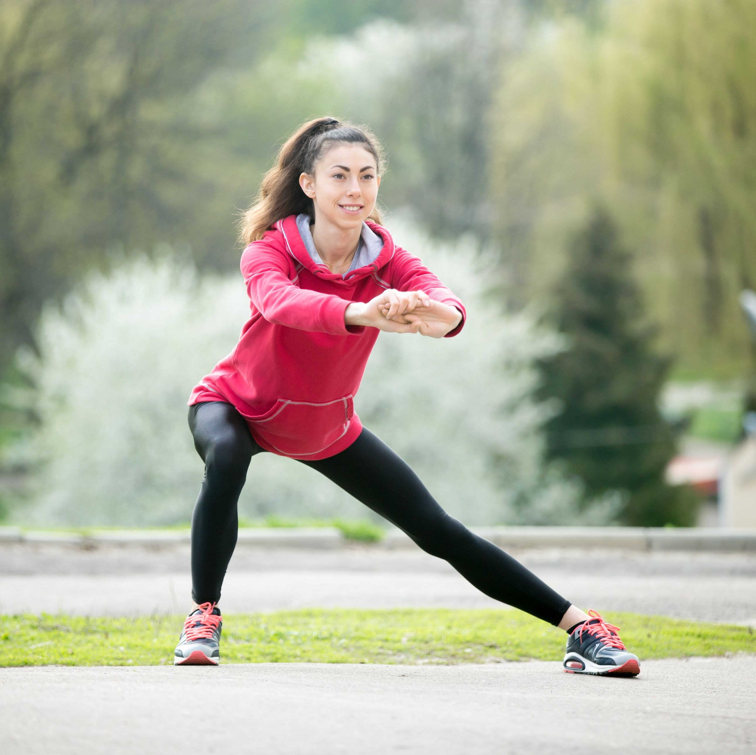Runner woman doing side lunges before jogging