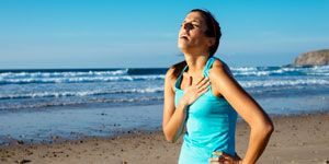 Exhausted female runner grasping her heart