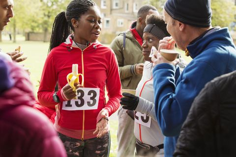 Runners drinking water and eating banana at charity race in park