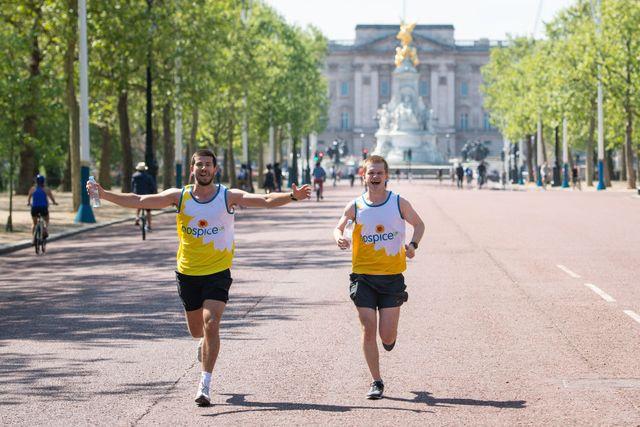 dos corredores corren por la avenida the mall de londres delante de buckhingham palace